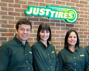 Just Tires associates standing in front of a Just Tires logo